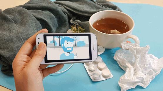 Hand mit Smartphone und Gesundheitsvideo vor Teetasse und Taschentüchern